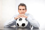 Businessman With Football At Work