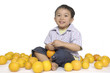 Funny portrait of little child sitting with orange fruit