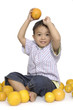 smiling little boy with many oranges ,isolated