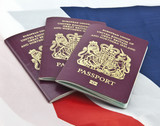 Three United Kingdom passports on folded Union Jack Flag