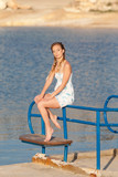 Barefoot girl in sundress posing on bench
