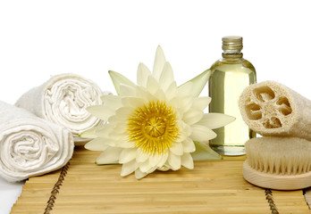 gerbera with massage oil and towel with brush on mat