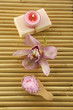 spa salt in wooden spoon and orchid with candle on mat