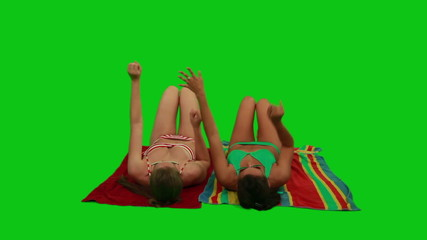 Girls lying on the towel and dancing with their hands
