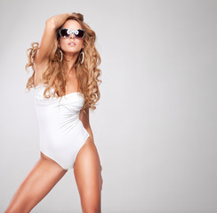 Young sexy woman with sunglasses on grey background