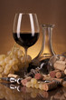 A bottle of red wine, jug and grapes on a golden background