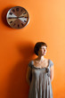 Young woman standing below a large clock on an orange wall