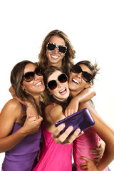 Happy young girls while taking pictures of themselves