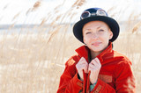 Happy woman wearing hat front of the reed
