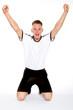 Fußballer in weißem Trikot jubelt und streckt Arme in die Luft