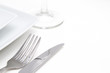 Place setting. white square plates with silver cutlery and glass