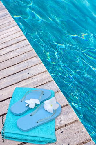 tongues et serviette sur passerelle de piscine