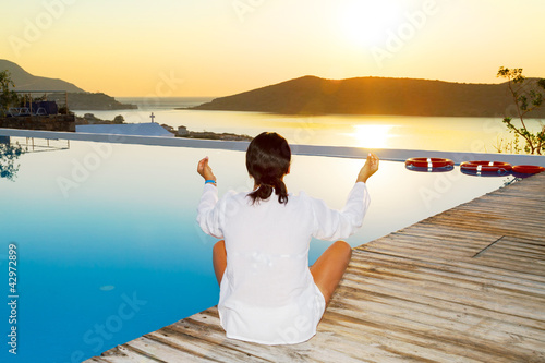 Woman meditating at sunrise in Greece