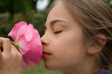 fillette sentant une rose