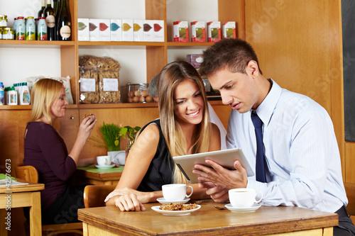 Paar schaut auf Tablet Computer im Café