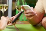 Fototapety Paar mit Smartphones im Restaurant
