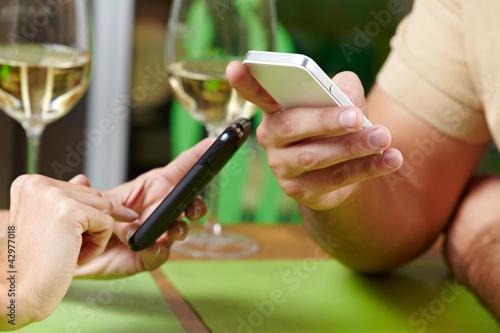 Paar mit Smartphones im Restaurant