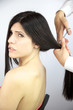 Beautiful woman getting hair cutted with sharp scissors