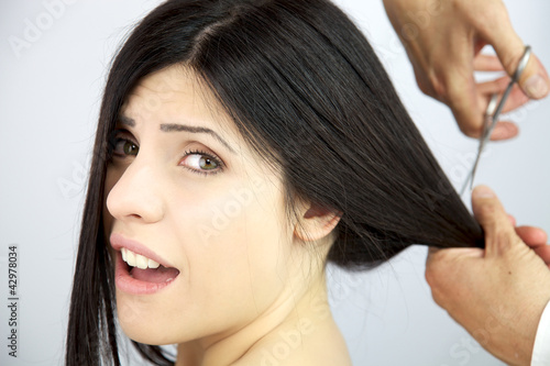 Beautiful woman screaming while her long hair are cut