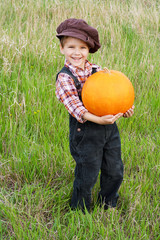 Smiling boy standing with pumpkin