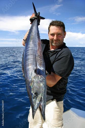 Fotobehang Vissen Lucky fisherman holding a beautiful wahoo fish