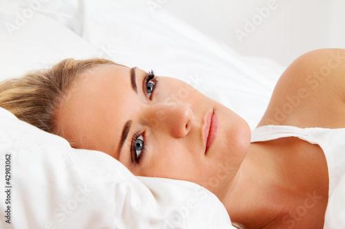 Frau liegt wach im Bett. Schlaflos und nachdenklic