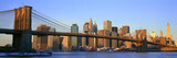 Panoramic view of Brooklyn Bridge and East River at sunrise with New York City, NY skyline post 9/11 view