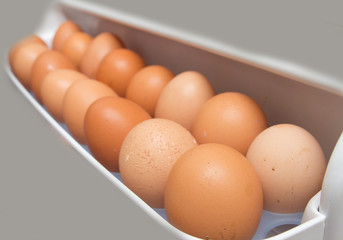 closeup of a pile of brown eggs in the fridge