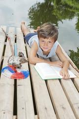 Kind liest beim Angeln