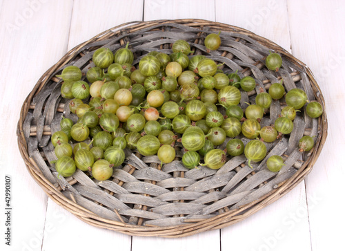 Green gooseberry on wicker mat on wooden background