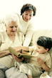 A young boy having fun learning from his grandmother and mother