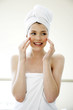 A woman with her hair and body wrapped up in towel smiling while applying under eye cream