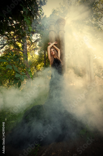 Mystic portrait of young woman in the forest ruins