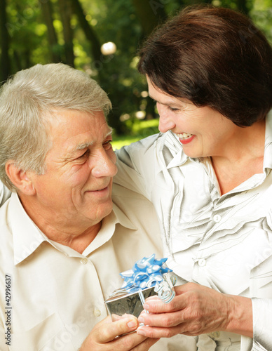 Mature happy smiling couple embracing in park with gift