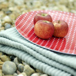 Three red apples on a folded picnic blanket