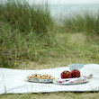 Bakewell tarts, red apples, cup and plastic forks on a picnic blanket
