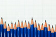 Row of pencils on a piece of graph paper