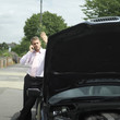 Businessman talking on the phone beside a broken down car