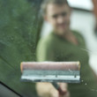 Man washing windshield with squeegee