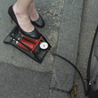 Businesswoman stepping on air pump