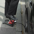 Businessman stepping on air pump