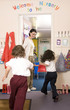Boy and girl running into classroom, woman watching