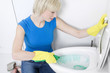 Woman with rubber gloves cleaning the toilet bowl