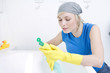 Woman with rubber gloves reading instructions on cleaning detergent