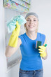 Woman with rubber gloves holding cleaning equipment