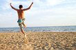 sporty young man jumping on beach