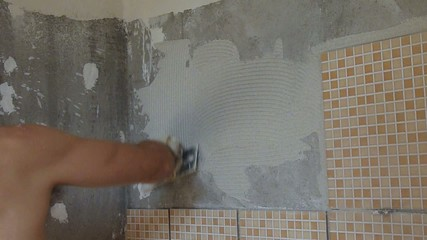 tiler spreading tile glue on a wall