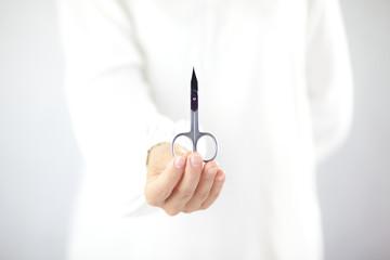 Kobieta trzymająca w ręku nożyczki do manicure