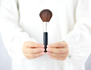 Kobieta trzymająca w dłoniach akcesoria do makijażu