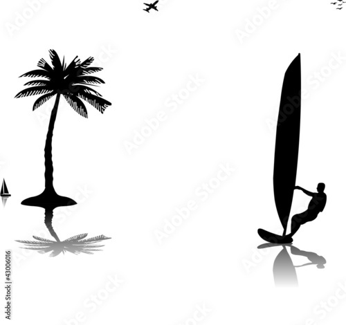 Silhouettes of man windsurfer at the sunset near the palm tree